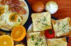 Petit déjeuner rustique - pain rôti avec du beurre et ciboulette, oeufs au plat et lard Photographie stock libre de droits