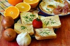 Petit déjeuner rustique - pain rôti avec du beurre et ciboulette, oeufs au plat et lard Photographie stock