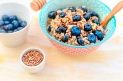 Petit déjeuner sain à haute valeur protéique, gruau de sarrasin avec des myrtilles, graines de lin et miel photographie stock