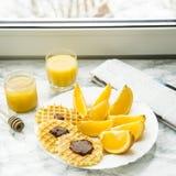 Petit déjeuner sain à une table de marbre avec le jus d'orange lisez un journal Photo libre de droits