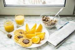 Petit déjeuner sain à une table de marbre avec le jus d'orange lisez un journal Photos libres de droits