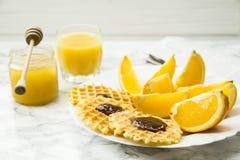 Petit déjeuner sain à une table de marbre avec le jus d'orange lisez un journal Image stock