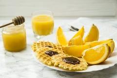 Petit déjeuner sain à une table de marbre avec le jus d'orange lisez un journal Images stock