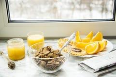 Petit déjeuner sain à une table de marbre avec le jus d'orange lisez un journal Photographie stock