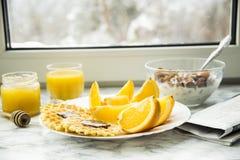 Petit déjeuner sain à une table de marbre avec le jus d'orange lisez un journal Images libres de droits