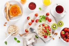 Petit déjeuner sain avec le gruau de farine d'avoine, fraise, écrous, pain grillé Photographie stock