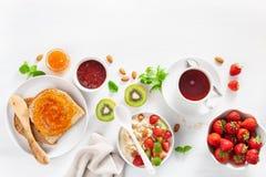 Petit déjeuner sain avec le gruau de farine d'avoine, fraise, écrous, pain grillé Photographie stock libre de droits