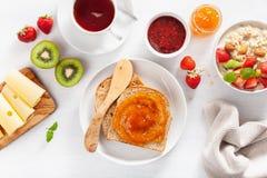 Petit déjeuner sain avec le gruau de farine d'avoine, fraise, écrous, pain grillé Image stock