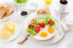 Petit déjeuner sain avec les oeufs au plat, l'avocat, la tomate, les pains grillés et le c Photographie stock