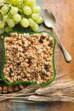 Petit déjeuner sain de muesli de granola avec du raisin, des écrous et des oreilles de blé images libres de droits