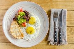 Petit déjeuner sain : Oeufs au plat, tomates, herbes et pain, avec des couverts, sur une table en bois Vue de ci-avant Image stock