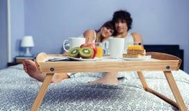 Petit déjeuner sain sur le plateau et couples se trouvant dedans Photos stock