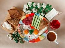 Petit déjeuner savoureux délicieux des oeufs, pain avec du beurre, saucisse du plat coloré Café, jus rouge avec les fleurs blanch Photos stock
