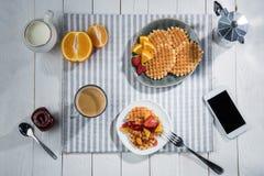 Petit déjeuner savoureux frais avec les gaufres et le smartphone avec l'écran vide sur la table Photo stock