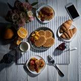 Petit déjeuner savoureux frais avec les gaufres et le smartphone avec l'écran vide sur la table Image stock