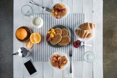 Petit déjeuner savoureux frais avec les gaufres, le café et le smartphone avec l'écran vide sur la table Image libre de droits