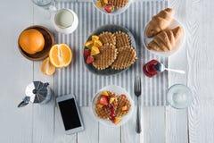Petit déjeuner savoureux frais avec les gaufres, le café et le smartphone avec l'écran vide sur la table Photographie stock