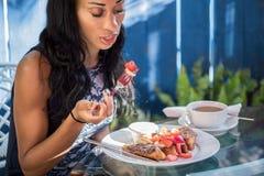 Petit déjeuner sur le patio : Une obscurité de Yong a pelé la fille ayant t français Images stock