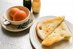 Petit déjeuner traditionnel asiatique de demi oeufs à la coque avec du pain de pain grillé Photos stock