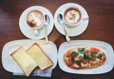 Petit déjeuner : une tranche de pizza, de pain, de café et de chocolat chaud dessus Photographie stock libre de droits