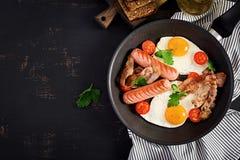 Petit d?jeuner anglais - oeuf au plat, tomates, saucisse et lard images stock