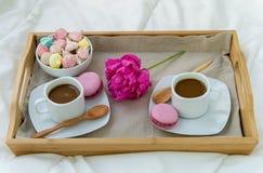 Petit d?jeuner dans le lit pour deux Plateau en bois avec du caf?, des macarons et Bizet photographie stock