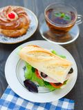 Petit déjeuner avec le sandwich, le thé et le gâteau Photos stock