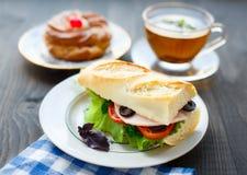 Petit déjeuner avec le sandwich, le thé et le gâteau Photographie stock