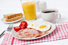 Petit déjeuner avec les oeufs au plat et le lard Image libre de droits