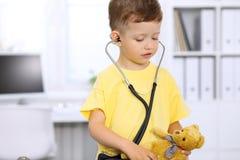 Petit docteur examinant un patient ntoy d'ours par le stéthoscope Photos stock