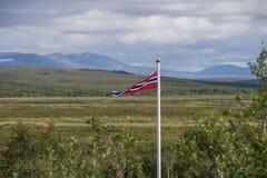 Petit drapeau norvégien avec le terrain plat derrière images libres de droits