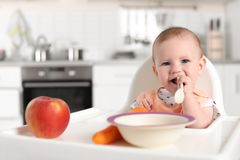 Petit enfant adorable prenant le petit déjeuner dans le highchair à l'intérieur photo stock