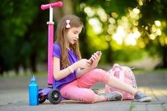 Petit enfant apprenant à monter un scooter en parc de ville le jour ensoleillé d'été Fille mignonne d'élève du cours préparatoire Photo stock