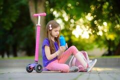 Petit enfant apprenant à monter un scooter en parc de ville le jour ensoleillé d'été Fille mignonne d'élève du cours préparatoire Photographie stock libre de droits