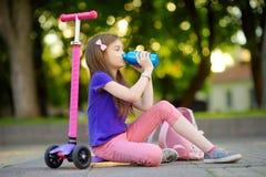 Petit enfant apprenant à monter un scooter en parc de ville le jour ensoleillé d'été Fille mignonne d'élève du cours préparatoire Images libres de droits