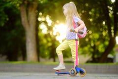 Petit enfant apprenant à monter un scooter en parc de ville le jour ensoleillé d'été Fille mignonne d'élève du cours préparatoire Photos libres de droits