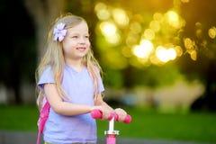 Petit enfant apprenant à monter un scooter en parc de ville le jour ensoleillé d'été Fille mignonne d'élève du cours préparatoire Image libre de droits