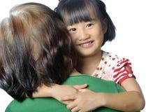 petit enfant asiatique souriant dans le bras de la femme supérieure Photos libres de droits