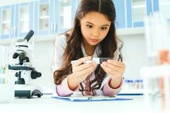 Petit enfant avec apprendre la classe dans l'observation d'échantillon de laboratoire d'école photo stock