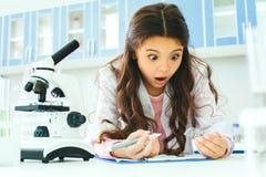 Petit enfant avec apprendre la classe dans le laboratoire d'école choqué photo stock