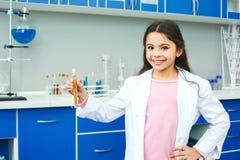 Petit enfant avec apprendre la classe dans le laboratoire d'école se tenant tenant la fiole photos stock