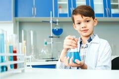 Petit enfant avec apprendre la classe dans le laboratoire d'école tenant l'ampoule images stock