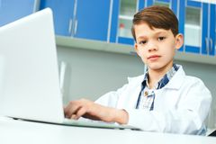 Petit enfant avec apprendre la classe dans le laboratoire d'école utilisant l'ordinateur portable Photos libres de droits