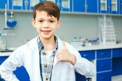 Petit enfant avec apprendre la classe dans le pouce de laboratoire d'école  Image stock