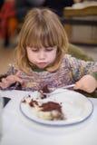 Petit enfant avec la cuillère mangeant le gâteau de chocolat Image libre de droits