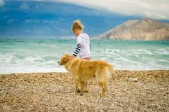 Petit enfant avec le chien dans la plage par la mer Images libres de droits