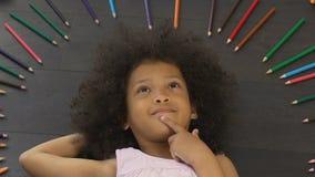 Petit enfant avec le grand mensonge Afro sur le plancher et la pensée à la nouvelle idée, imagination banque de vidéos