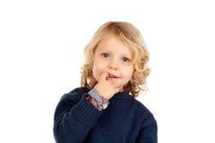 Petit enfant blond bitting ses clous image stock