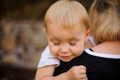 Petit enfant blond se trouvant sur l'épaule du ` s de maman avec les yeux fermés images stock