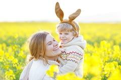 Petit enfant d'enfant en bas âge et sa mère dans des oreilles de lapin de Pâques ayant Photos stock
